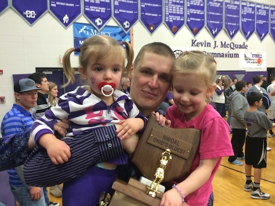 Following their league championship, Swanton head coach Matt Smith embraces the trophy along with his two daughters, Kinsley (left) and Rylee. Smith, a former Paulding Panther and 2000 graduate, has his team in the Division III district tournament and will play Delta on Thursday at Anthony Wayne High School.